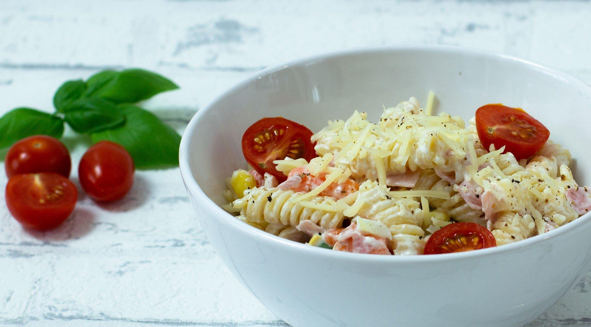 Nudelsalat mit frischen Tomaten und Käse bestreut