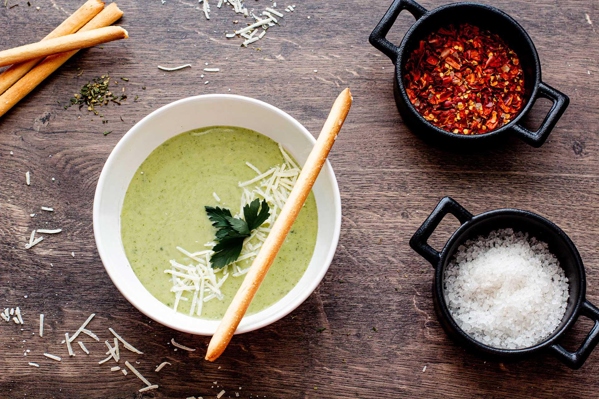 Auf dem Bild ist ein Teller mit Zucchinicremesuppe zu sehen, als Dekoration dienen Grissini sowie geriebener Hartkäse, Salz und Chiliflocken in kleinen Schälchen.