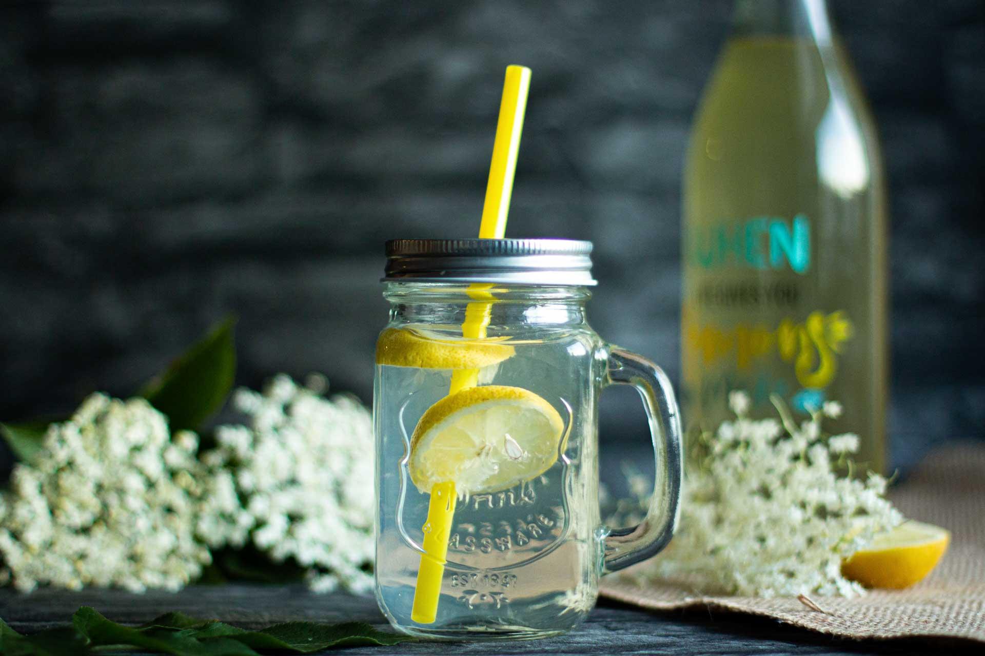 Glas mit Holunderblütensirup, Zitronen, Sirupflasche, frische Zitronen auf Juteband