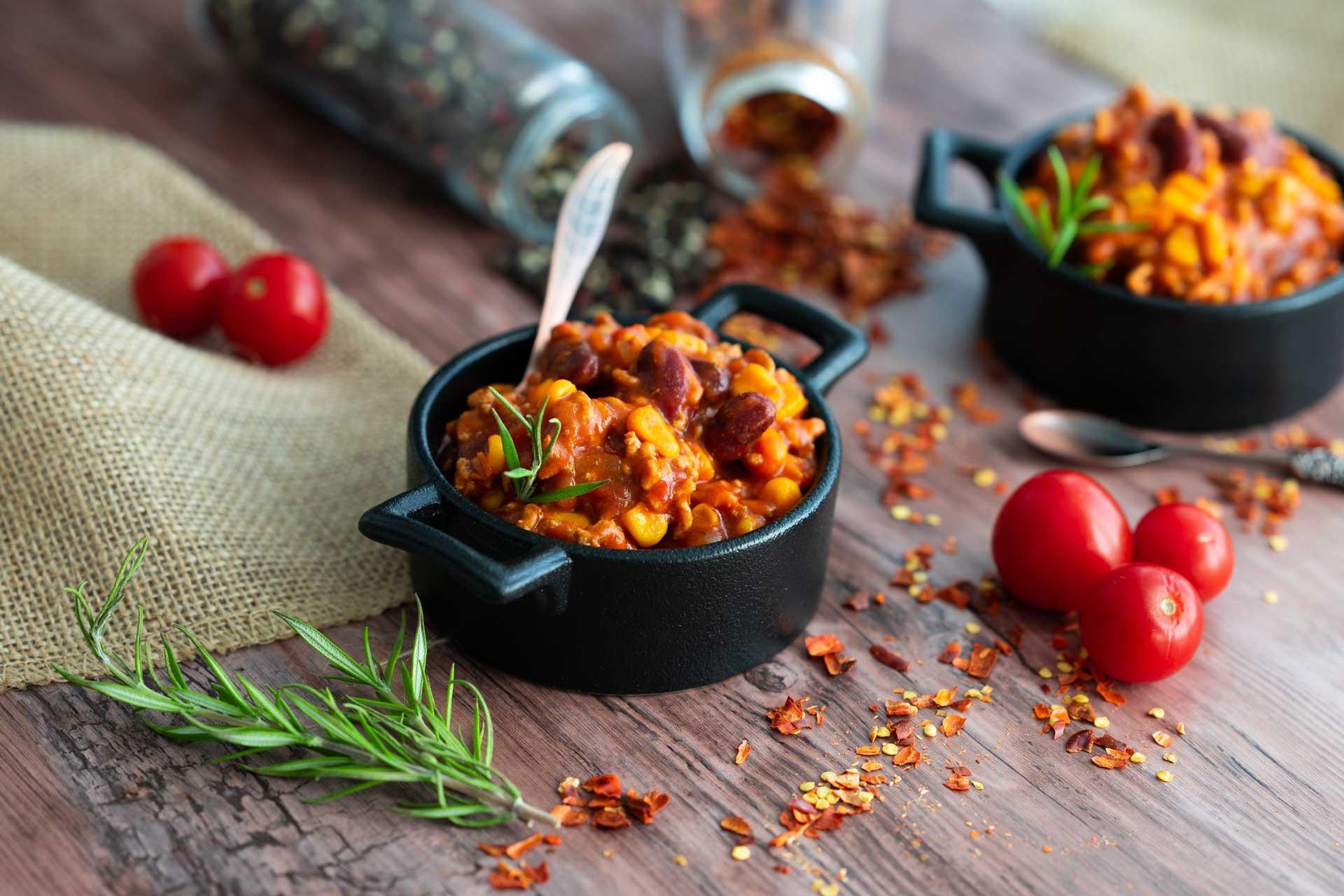 Chili con carne in kleinen Schüsserl, mit frischen Tomaten, Chiliflocken und Rosmarinzweigen