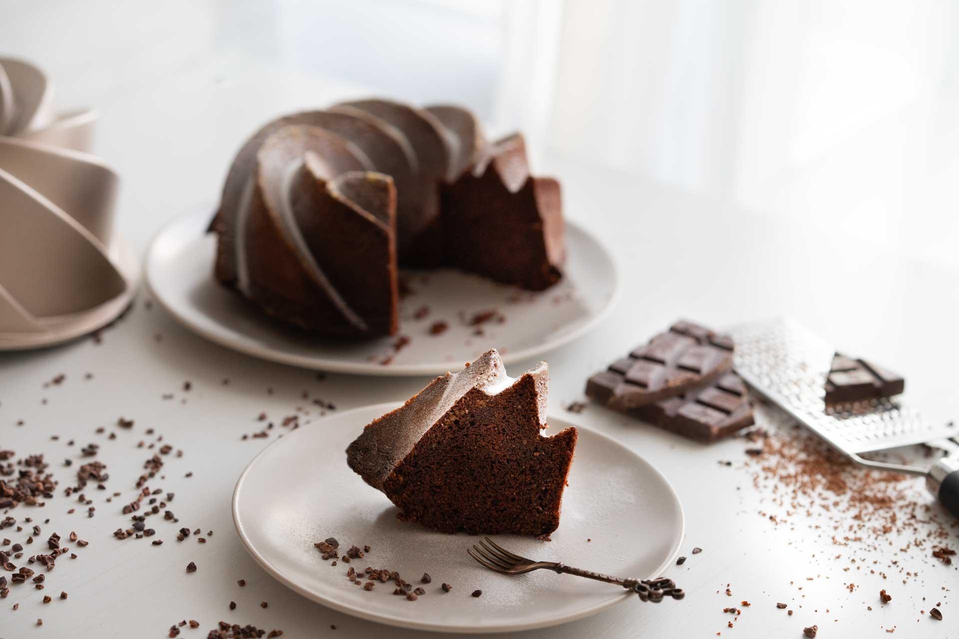 saftiger Schokoladekuchen mit Schokoraspeln und kleiner Gabel auf einem Teller