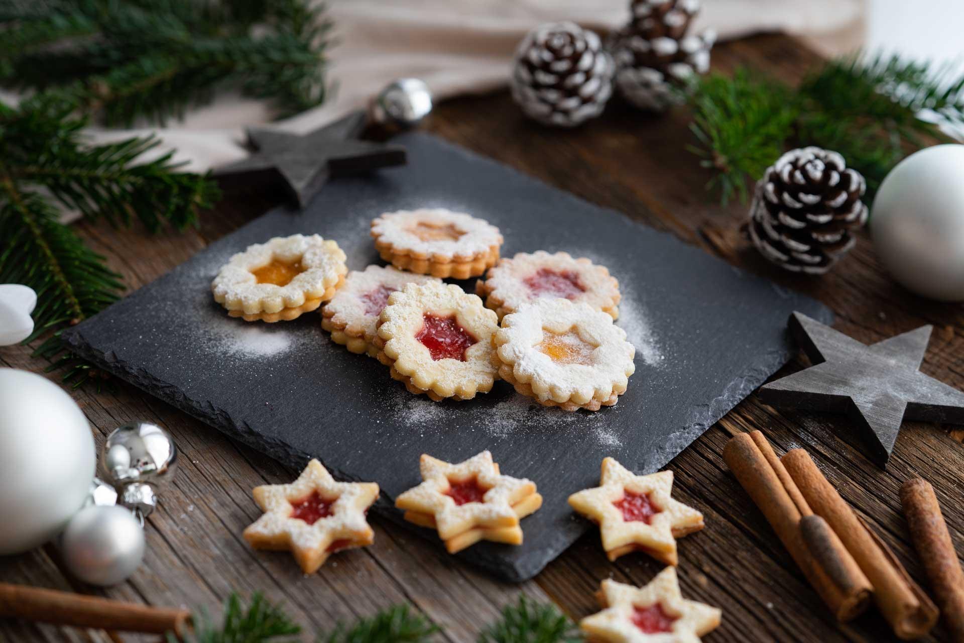 Kekse mit Loch, mit Marmelade gefüllt, Staubzucker bestreut