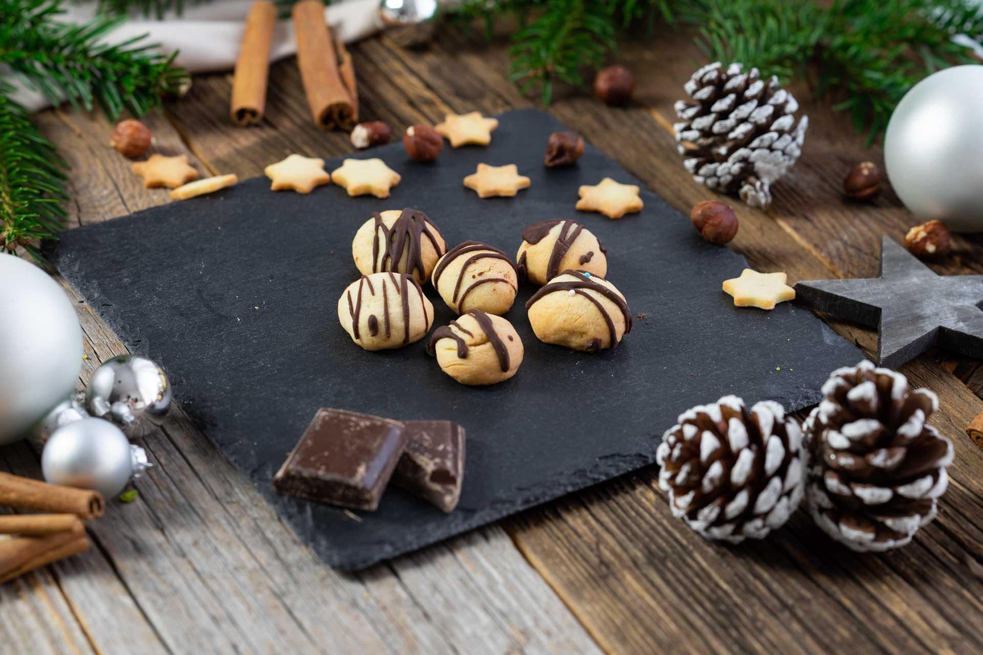 kleine Keksgugeln mit Schokolade garniert, weihnachtlicher Hintergrund