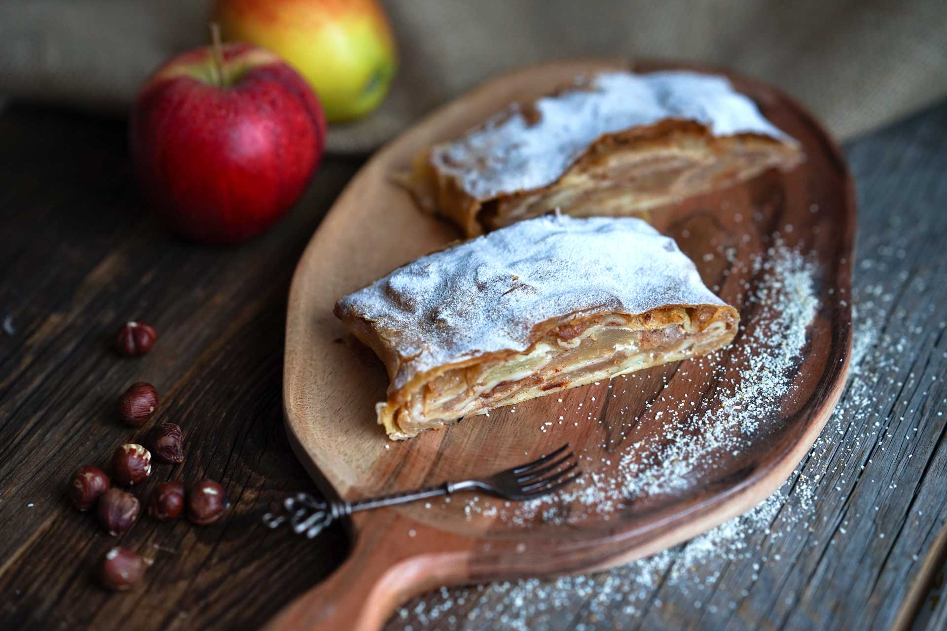 Apfelstrudel aufgeschnitten, frische Nüsse und Äpfel