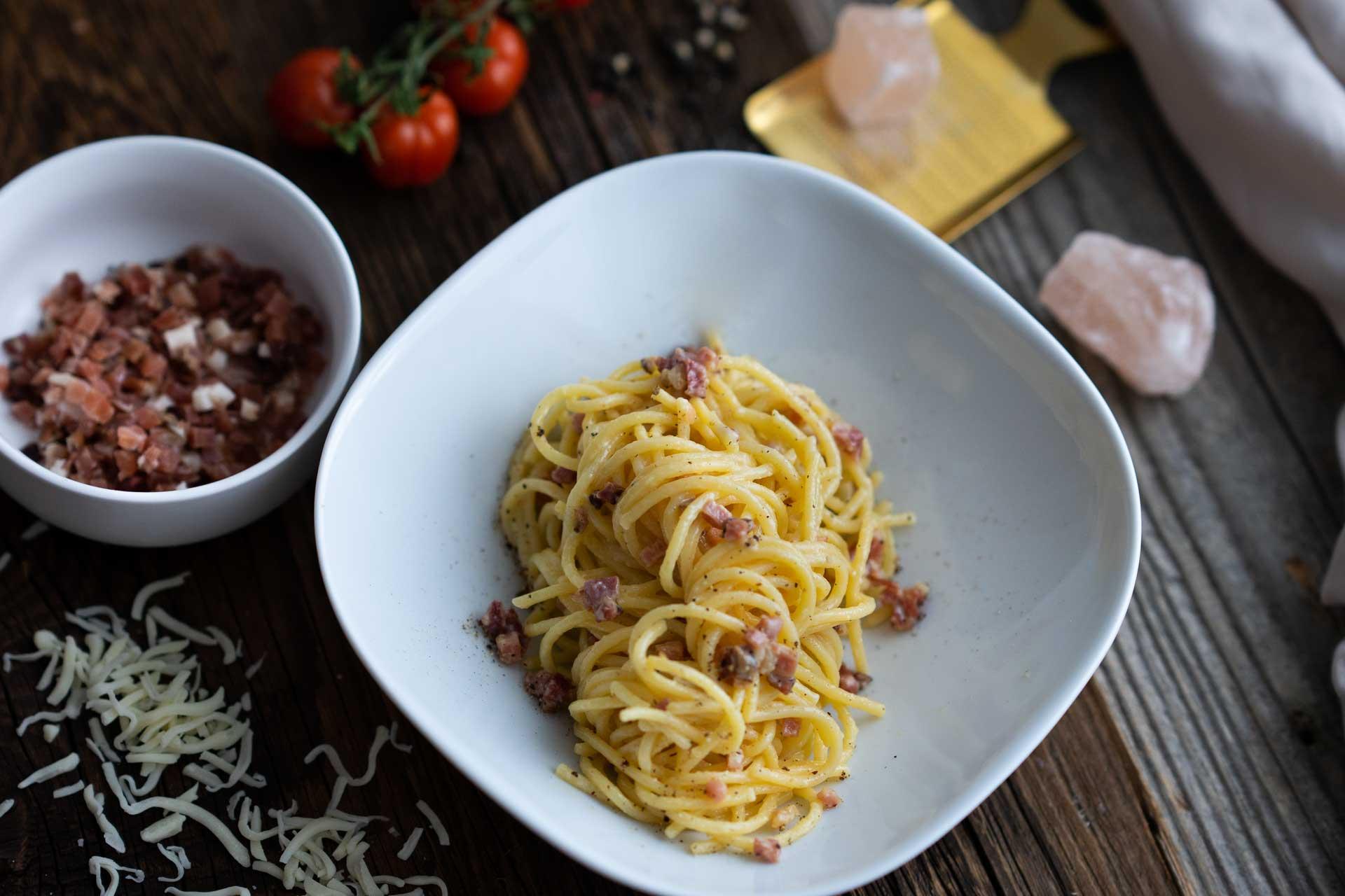 Spaghetti Carbonara mit Speck garniert, daneben Speck in einer Schüssel und Tomaten